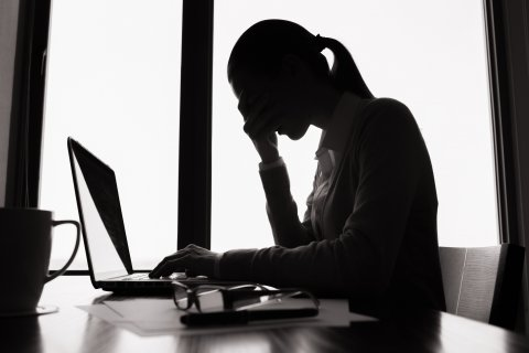 woman worried about student loans at her computer