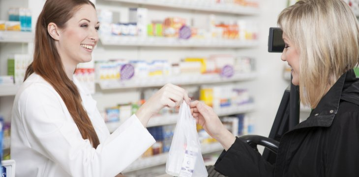 Pharmacy Technician handing medicine to patient