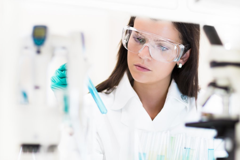 Woman practicing lab safety at work