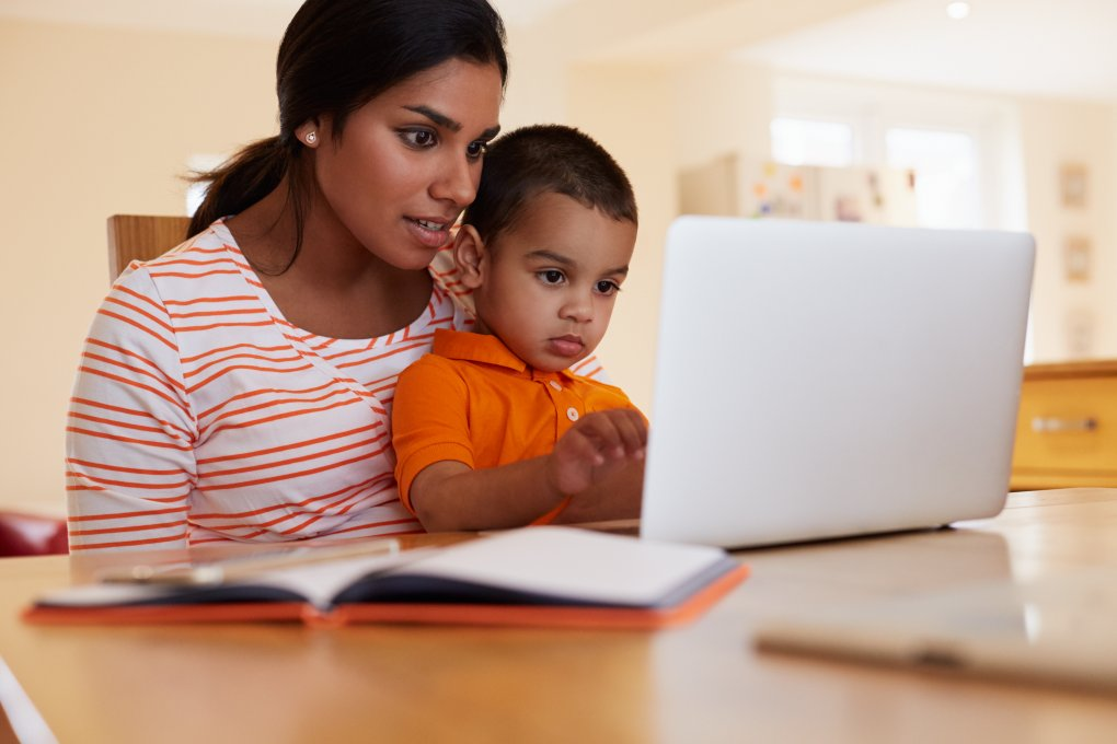 Mom taking an online course with son on her lap