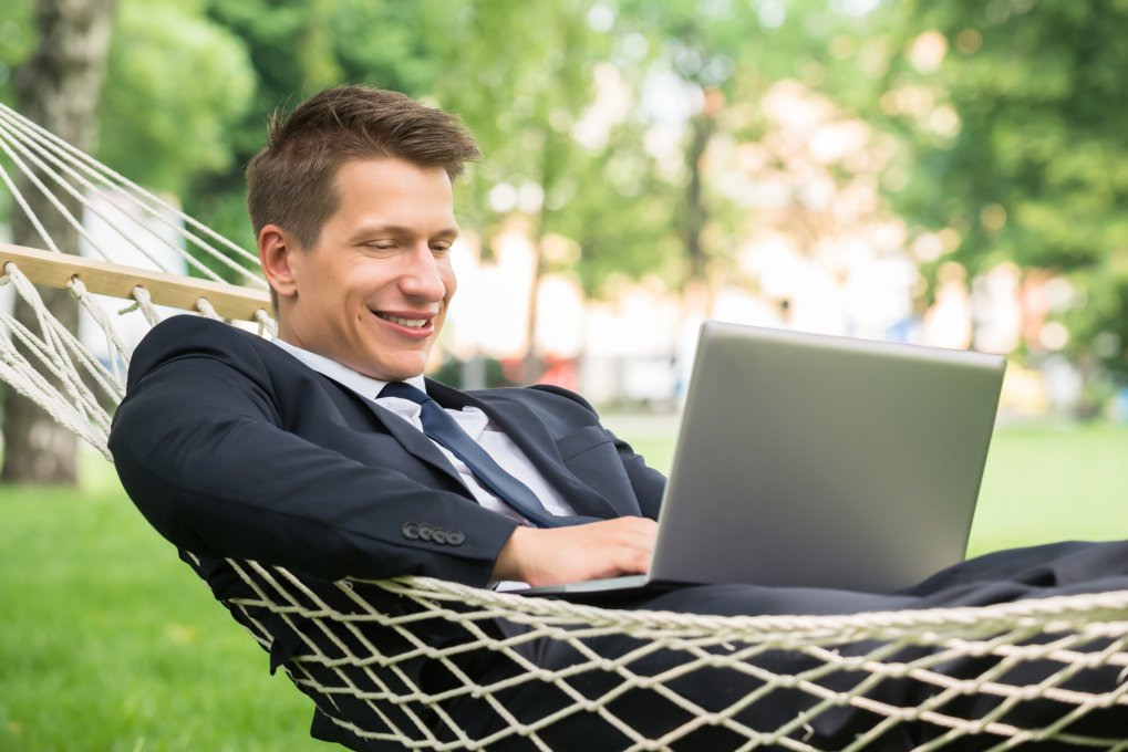 Man Learning Online while sitting in a hammock.