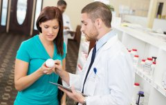 Pharmacy Technician assisting a woman in scrubs with a medication